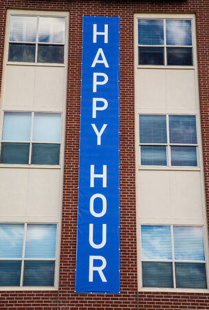 Blue Happy Hour sign on a brick and stucco building Imagens - 28510583