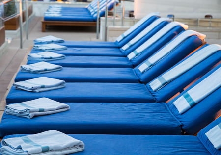 lounges: Rows of chaise lounges at a spa with blue towels Stock Photo