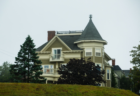 An old olive green victorian house on a grassy hill under foggy skies
