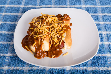 smothered: Two hot dogs on a white plate smothered in beef chili and shredded cheddar Cheese