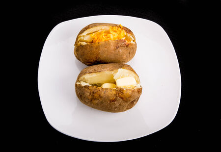 jacket potato: Two baked potatoes on a white plate and black background. One with butter and one with cheese