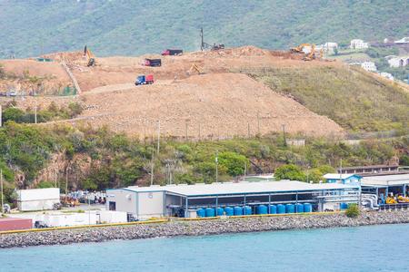 Dump Trucks on hilltop construction over an industrial port