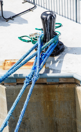 Frayed blue rope looped around an old black bollard on pier Stock Photo