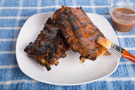 peppery: Barbecue spare ribs on a white place with peppery sauce Stock Photo
