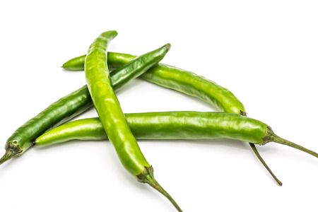 Green cayenne peppers on a white background