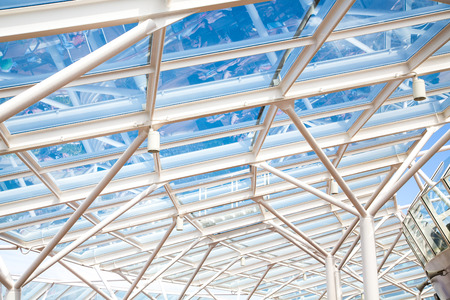 A clear glass atrium roof under blue sky supported by white steel Stock Photo
