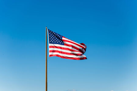 An American flag against a blue sky on an old rusty flagpole