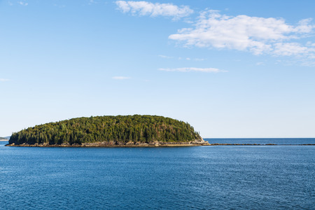An evergreen covered island in deep blue water under nice skies Imagens