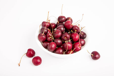 A white bowl of cherries on a white table