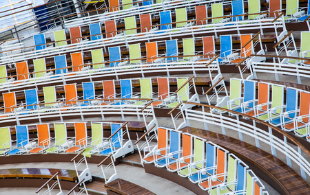 curving: Rows of colorful canvas chairs curving around an outdoor arena
