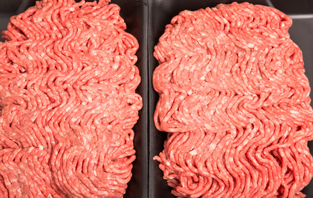 Fresh, raw ground beef in a black, styrene tray Stock Photo