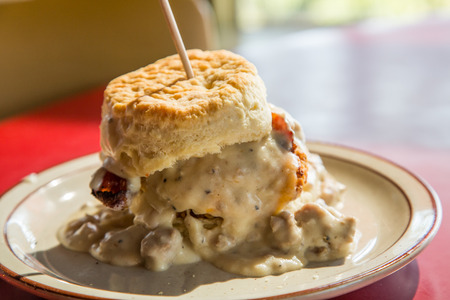 A massive breakfast sandwich of fried chicken, bacon and cream gravy on a biscuit