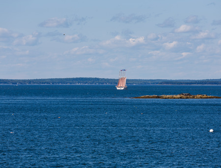 schooner: A four masted schooner touring sightseers through a blue harbor off Bar Harbor, Maine