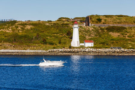 A white pleasure boat speeding past a lighthouse in blue water photo