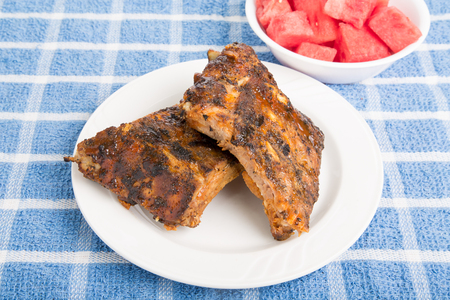 barbecue ribs: Barbacoa costillas en un plato blanco con sand�a cortada en un taz�n Foto de archivo