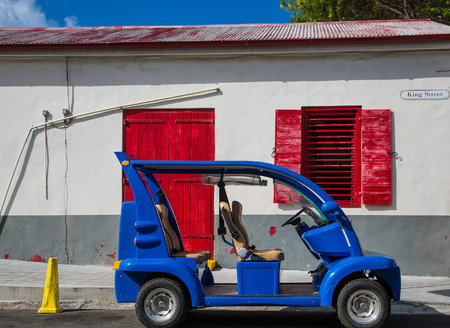 king street: A small electric car on King Street in St Croix in front of an old white and red building