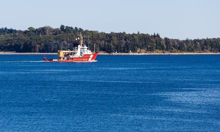 An orange Canadian coast guard boat on deep blue water near Halifax, Nova Scotia