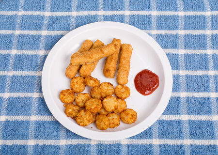 Fried fish sticks on white plate with cocktail sauce and potato puffs photo