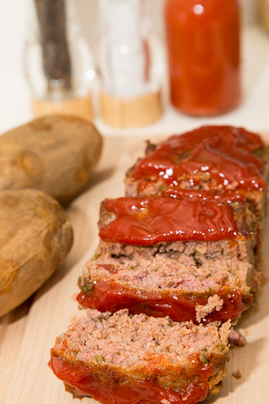 Sliced meatloaf on a wood cutting board with baked potatoes Stock Photo