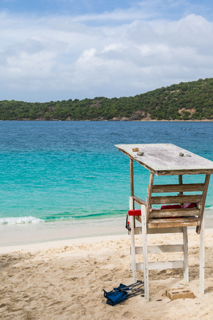 Old wood lifeguard stand on beach by blue water photo