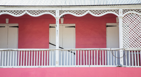 white trim: An old pink building with white trim on balcony
