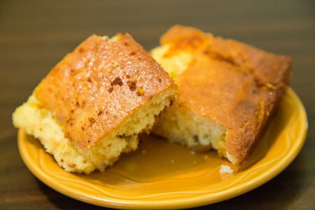 Two pieces of fresh baked corn bread on a yellow plate on table