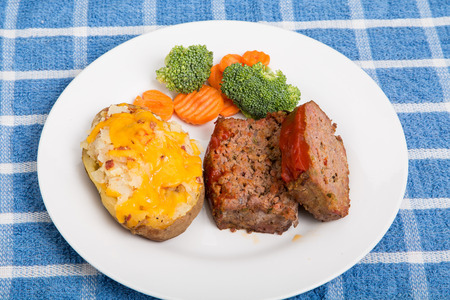 Fresh sliced meatloaf with twice baked potato and broccoli and carrots photo