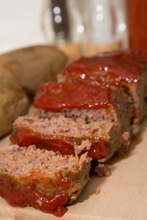 Sliced meatloaf on a wood cutting board with baked potatoes photo