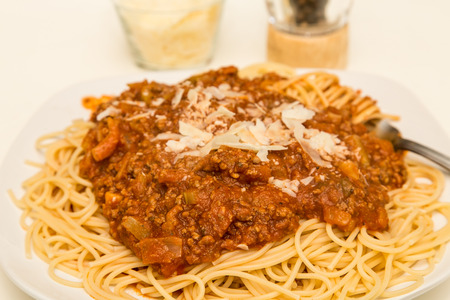 A plate of spaghetti with bolognese sauce and shaved parmesan cheese