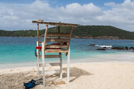 An old white wood lifeguard chair on a tropical beach photo