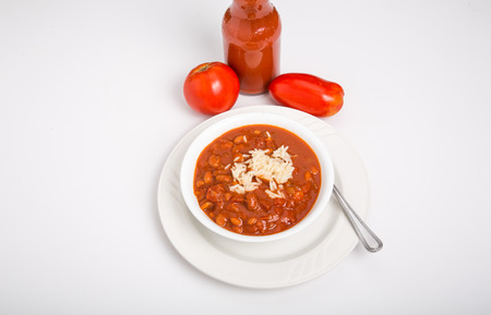A bowl of chili con carne with beans and white rice with two fresh tomatoes and a bottle of hot sauce photo