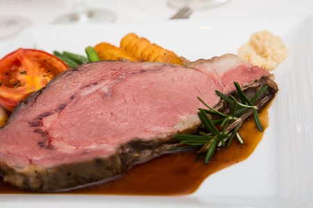 A nice slab of rare prime rib on a plate with gravy, rosemary and vegetables