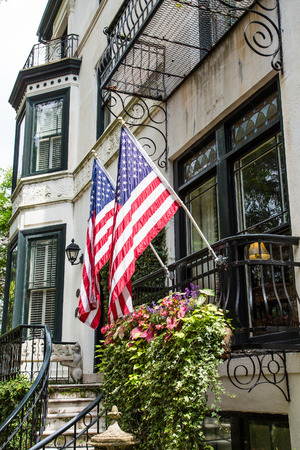 Two American flags on railing of a classic old home in Savannah, Georgia photo