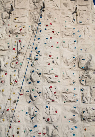 A rock climbing wall with blue rope and bells at top