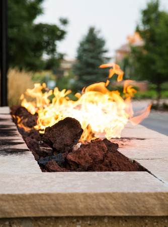 An outdoor fireplace burning at dusk