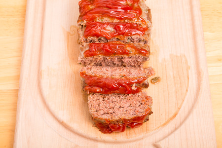 A fresh baked meatloaf sliced on a wood cutting board