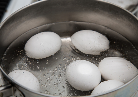 boiling: Six eggs boiling in a saucepan