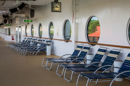 lounges: A row of blue and white chaise lounges on a cruise ship deck under large portholes