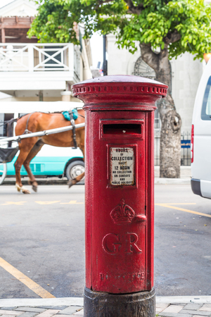 Old British style mailbos on a street in Nassau with horse and buggy in background