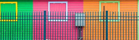 orange nassau: Bright colorful walls behind blue fence in Nassau, Bahamas