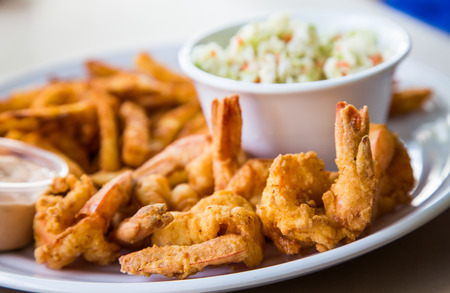 A fried shrimp dinner with french fries, coleslaw and sauce Stock Photo