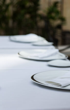 white linen: White plates and napkings on white linen tablecloth