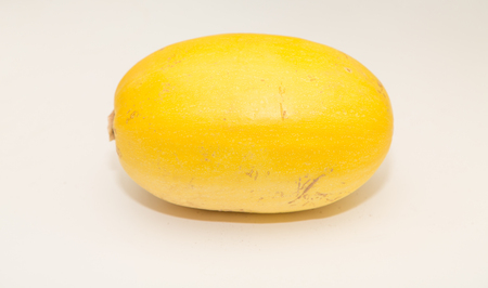 A whole spaghetti squash on a white counter
