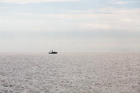 shrimp boat: A shrimp boat pulling a net in sillouette