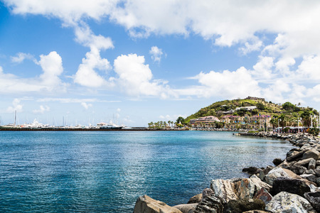seawall: A rock seawall curving toward a modern shopping mall and a luxury yacht marina Stock Photo
