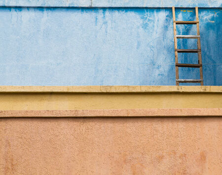 An old wooden ladder leaning against a blue stucco wall over yellow and orange walls