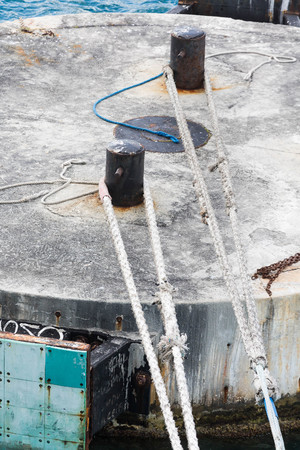 mooring bollards: White ropes tied to black bollards on a concrete mooring platform