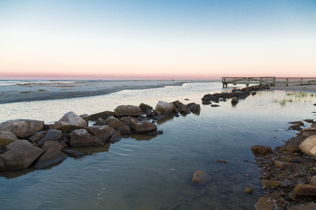 seawall: A rock seawall on the coast in a harbor Stock Photo