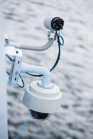 bulkhead: White security camera over ocean on the white bulkhead of a ship