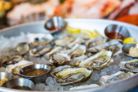 ostra: Una bandeja de ostras frescas en media concha sobre hielo con salsa
